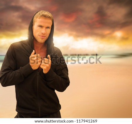 Portrait of a handsome young man on the beach at sunset - stock photo