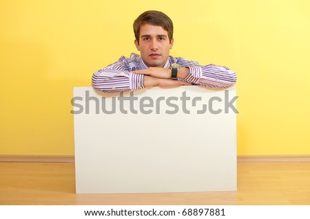 Portrait of a handsome young man peeping over a blank billboard against uniform background - stock photo