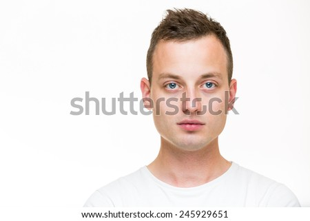 Portrait of a handsome young man, perfectly calm, facing the camera with emotionless expression - stock photo