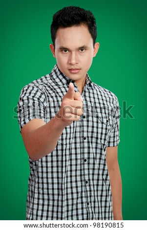 Portrait of a handsome young man pointing finger at you against green background