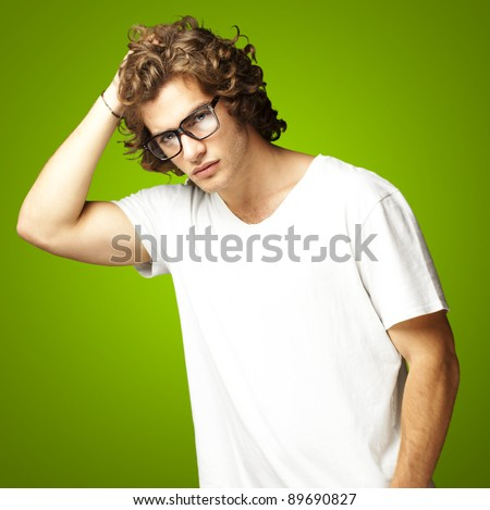portrait of a handsome young man posing against a green background - stock photo