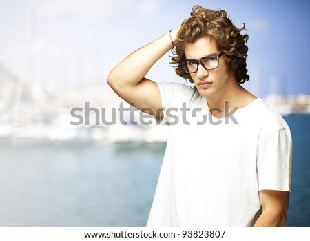 portrait of a handsome young man posing against a harbor background - stock photo