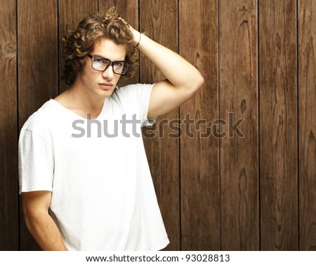 portrait of a handsome young man posing against a wooden wall - stock photo