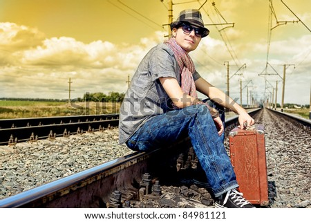 Portrait of a handsome young man posing at a railroad. - stock photo