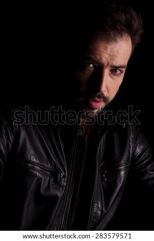 Portrait of a handsome young man posing on dark studio background.