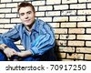 Portrait of a handsome young man posing over brick wall. - stock photo