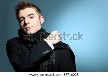 Portrait of a handsome young man posing over grey background. - stock photo