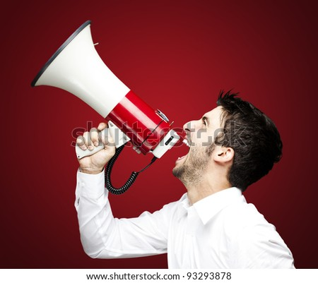 portrait of a handsome young man shouting using a megaphone over a red background - stock photo