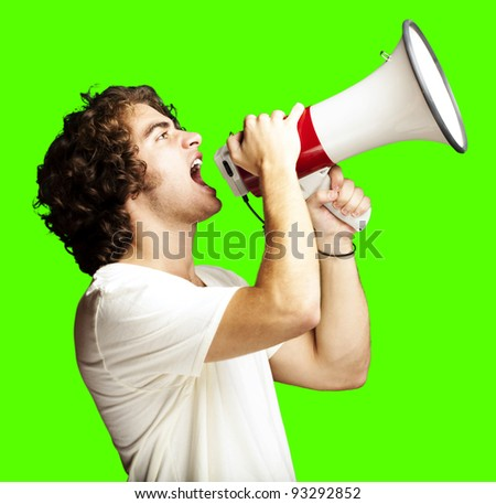 portrait of a handsome young man shouting with a megaphone against a removable chroma key background - stock photo