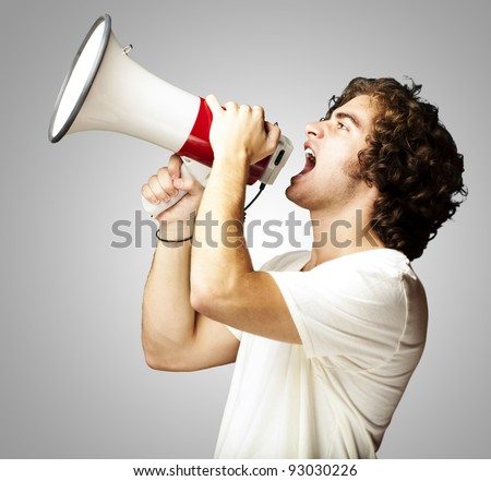 portrait of a handsome young man shouting with megaphone against a grey background - stock photo