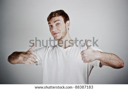 Portrait of a handsome young man showing thumbs up