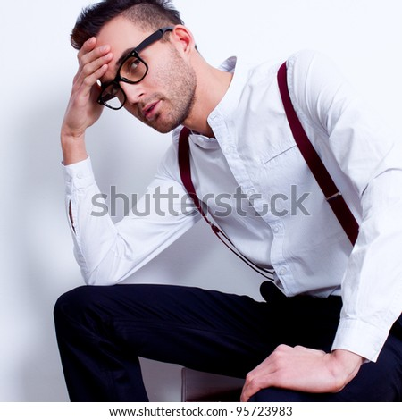 portrait of a handsome young man sitting in white shirt and suspenders against white background - stock photo