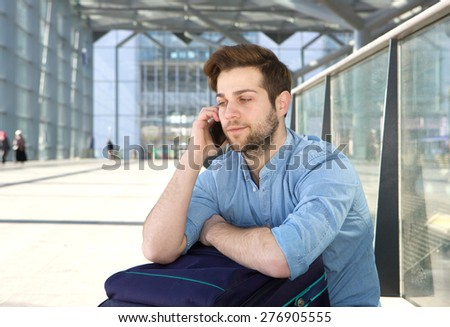 Portrait of a handsome young man sitting on floor waiting for next flight and talking on mobile phone - stock photo