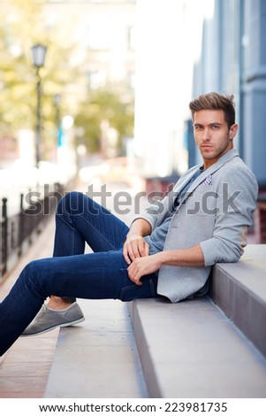 portrait of a handsome young man sitting  outside on the stairs - stock photo