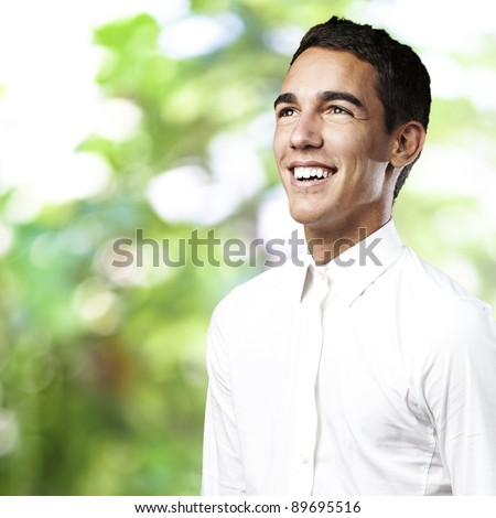 portrait of a handsome young man smiling against a nature background