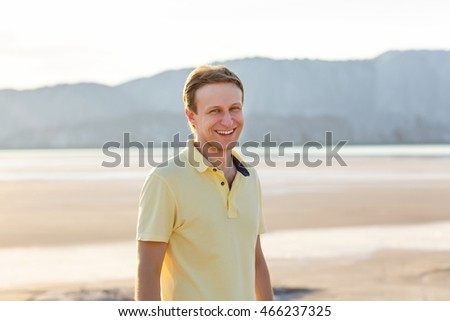 Portrait of a handsome young man smiling against mountain