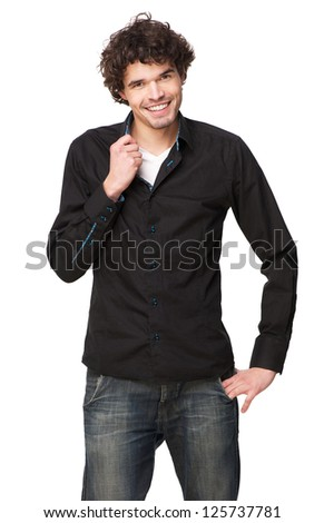 Portrait of a handsome young man smiling and holding his shirt collar - stock photo