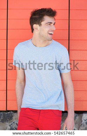 Portrait of a handsome young man smiling and looking away - stock photo