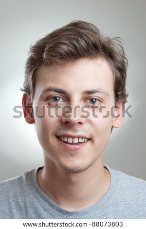 portrait of a handsome young man smiling at camera, isolated on gray