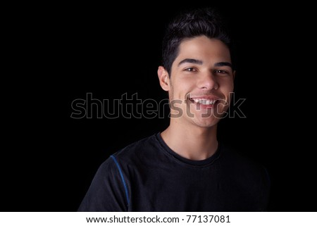 Portrait of a handsome young man smiling, on black background. Studio shot. - stock photo