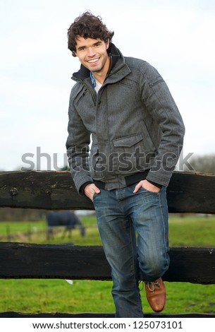 Portrait of a handsome young man smiling outdoors - stock photo