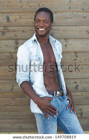 Portrait of a handsome young man smiling outdoors with open shirt