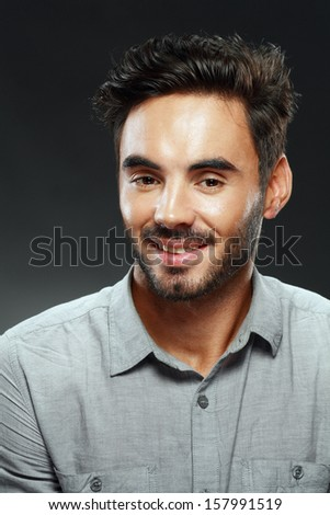 portrait of a handsome young man smiling studio shot - stock photo