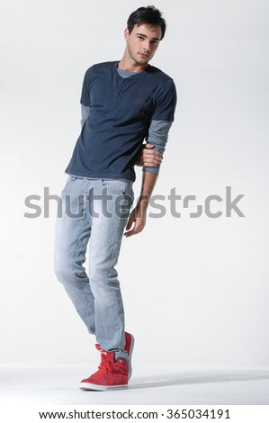 Portrait of a handsome young man standing in studio - stock photo