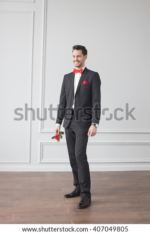 Portrait of a handsome young man. Stylish hairstyle, red bow tie and handkerchief in pocket, white shirt, black suit. Showman, groom smiling and holding a red rose.