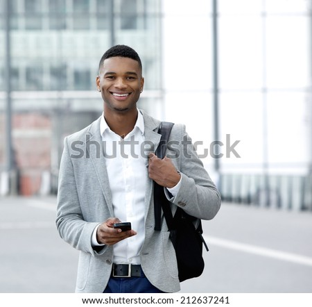 Portrait of a handsome young man text messaging on mobile phone - stock photo