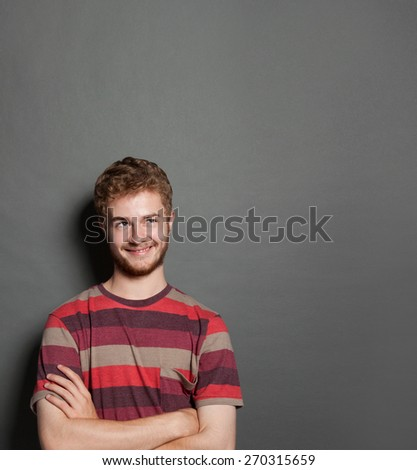 Portrait of a handsome young man thinking and smiling against grey background - stock photo