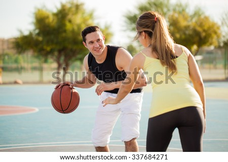 Portrait of a handsome young man trying to score some points during a basketball game against his date - stock photo