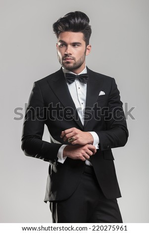 Portrait of a handsome young man wearing a tuxedo, looking away from the camera while ajusting his button. - stock photo