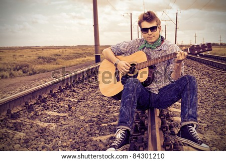 Portrait of a handsome young man with a guitar on a railroad. - stock photo
