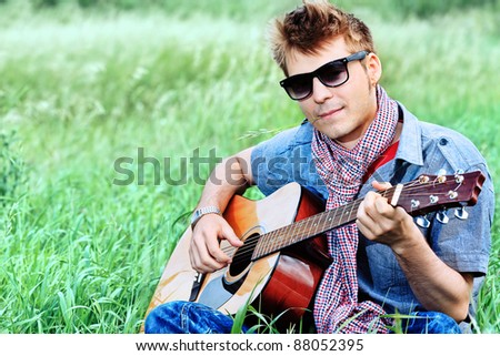 Portrait of a handsome young man with a guitar outdoor. - stock photo