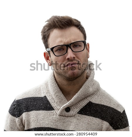 Portrait of a handsome young man with a perplexed expression, against a white background - stock photo