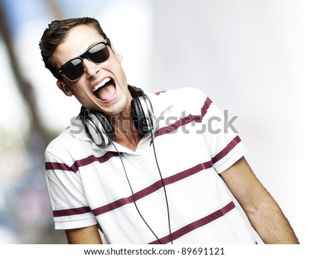 portrait of a handsome young man with headphones against a city background - stock photo