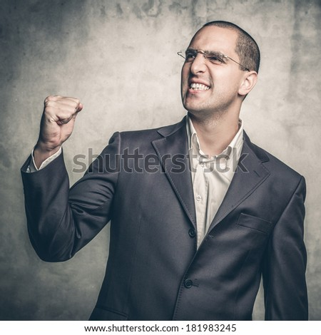 Portrait of a handsome young man with his arm raised in triumph - stock photo
