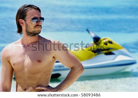 Portrait of a handsome young man with his water scooter - stock photo