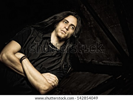 Portrait of a handsome young man with long hair. Low key - stock photo