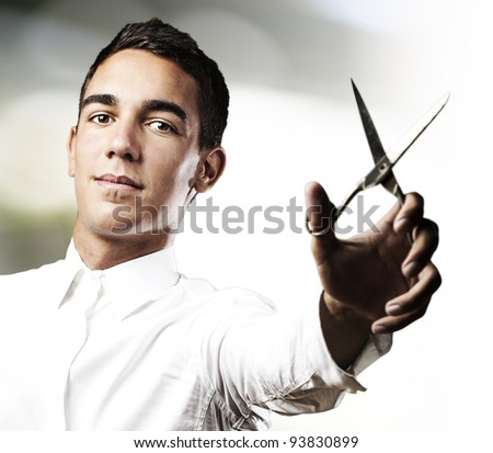 portrait of a handsome young man with scissors in a house - stock photo
