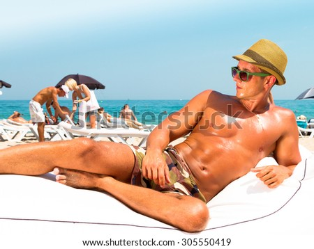 Portrait of a handsome young muscular man in military printed trousers and hipster retro straw hat in luxury beach resort,laying on beach chair ,relaxing getting fun and sunbath  on summer vacation - stock photo