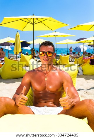 Portrait of a handsome young muscular man in white swimtrunks with luxury beach resort background,sitting on beach chair and showing super sign,getting fun on summer vacation - stock photo