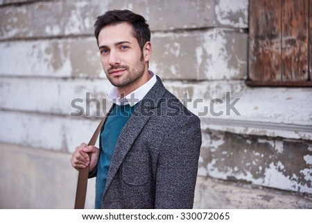 Portrait of a handsome young professional standing on a city street with a vintage feel looking at the camera confidently - stock photo