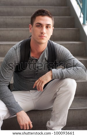 portrait of a handsome young student, sitting on steps inside a school - stock photo