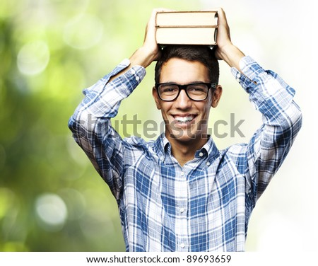 portrait of a handsome young student smiling and holding books on his head against nature background - stock photo