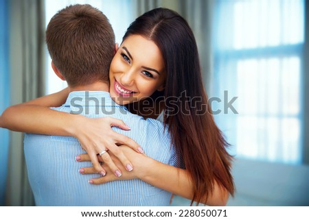 Portrait of a happiness woman hugging his boyfriend at home - stock photo