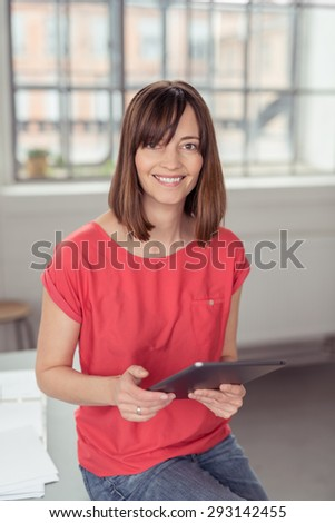 Portrait of a Happy Adult Woman Sitting on the Table inside the Office, Holding her Tablet Computer While Looking at the Camera. - stock photo