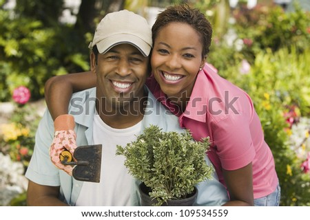 Portrait of a happy African American couple gardening together - stock photo