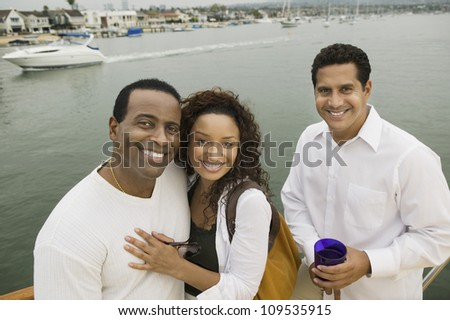 Portrait of a happy African American couple with friend on yacht